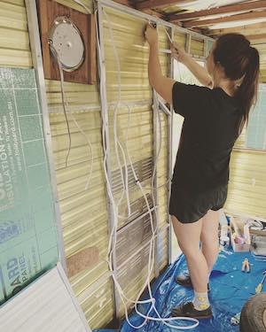 Woman wiring 12v in walls of vintage caravan