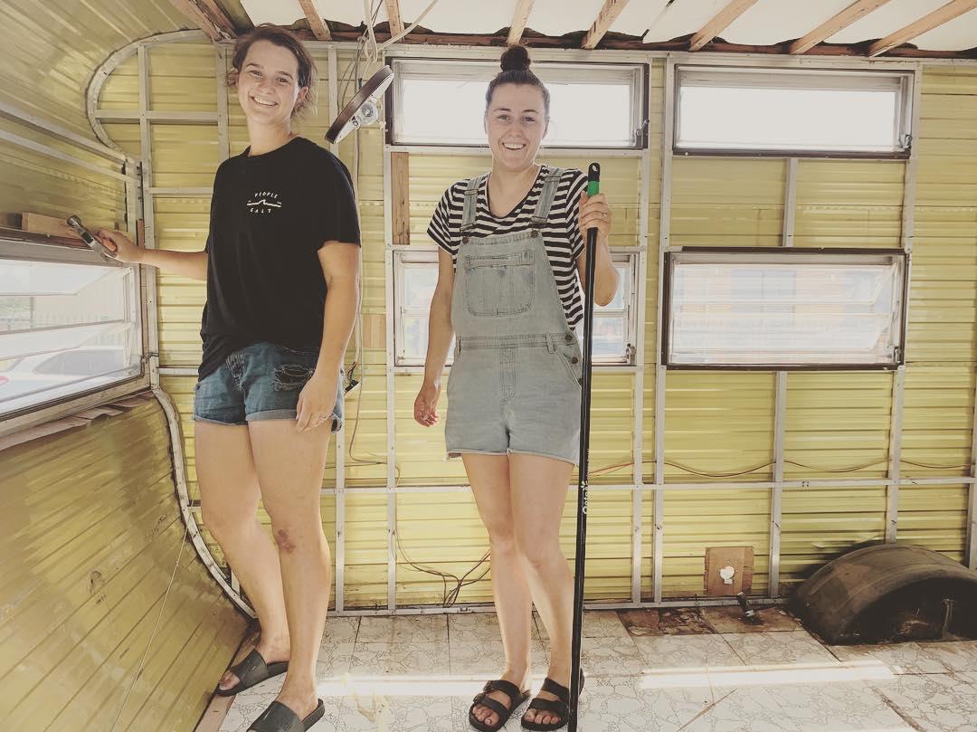 Two women standing inside a gutted vintage caravan