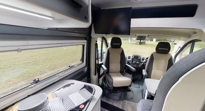 Interior view of Avida Escape campervan looking from the back area into the drivers seat