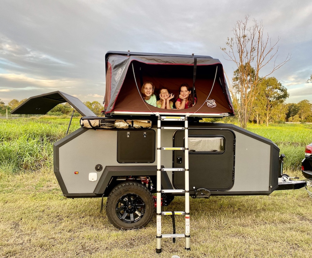 3 Children inside a rooftop tent on top of an off road teardrop camper