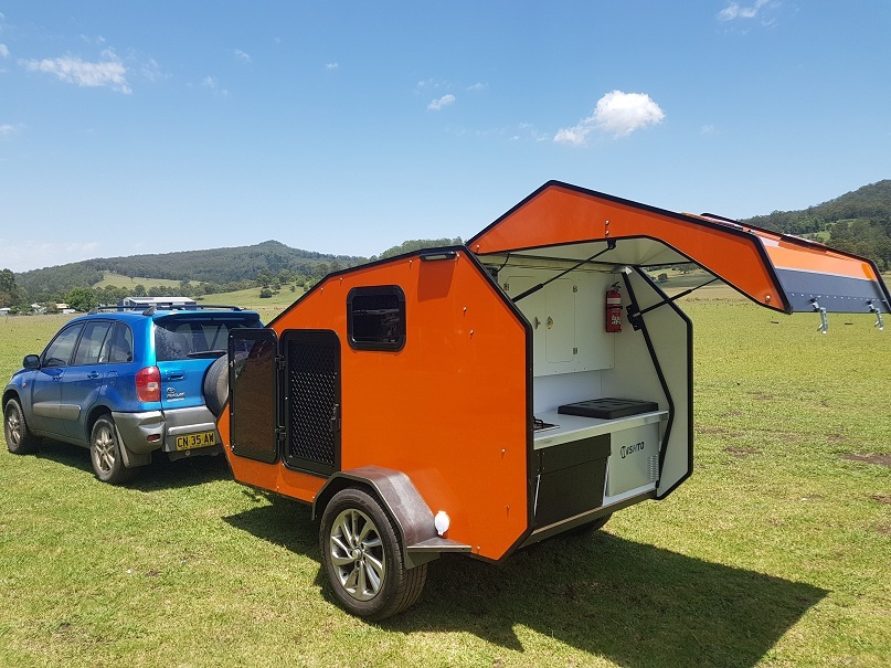 Orange teardrop camper hooked up to a Rav4