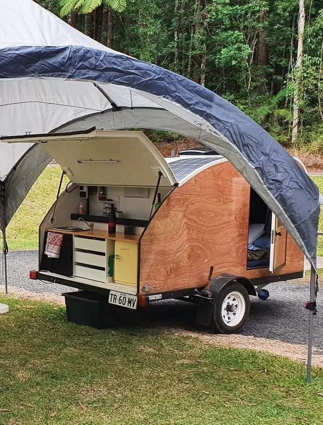Wotpods teardrop camper set up for camping with the rear kitchen hatch open