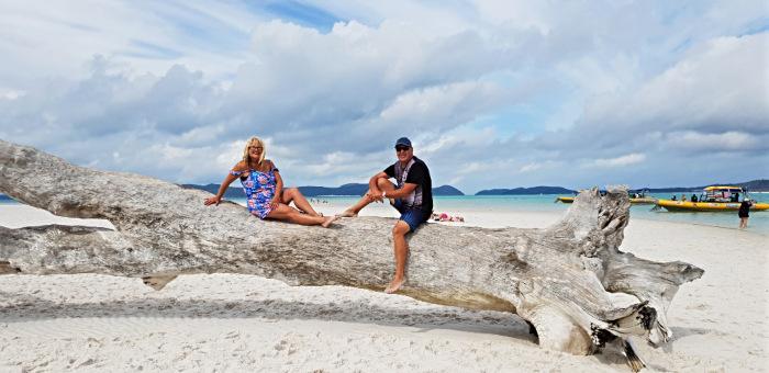 Couple sitting on tree log on white, sandy beach