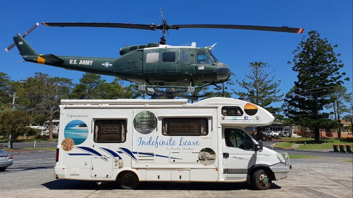 Motorhome parked in front of display US Army helicopter
