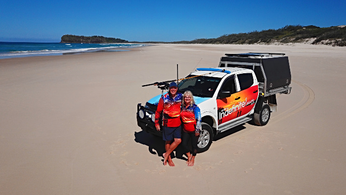 Couple standing in front of their ute on Fraser Island