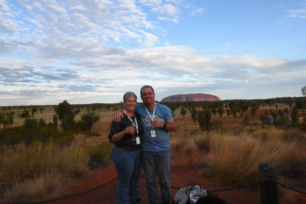 Man and woman standing in front of Uluru / Ayers Rock, holding a glass of wine