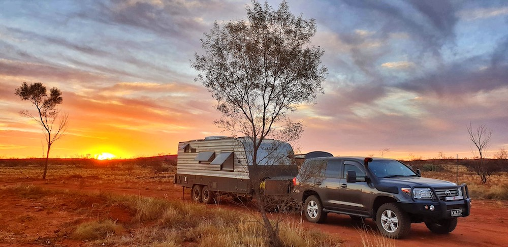 Car and caravan in the Australian outback at sunset