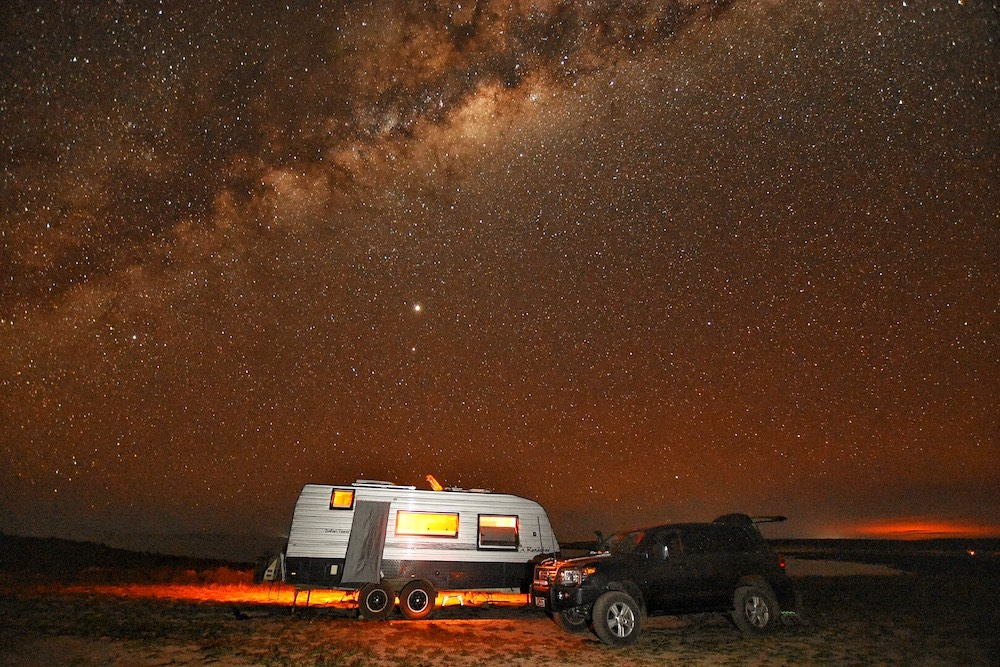 Car and caravan under a starry sky