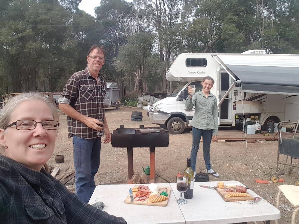 Mum, dad and child having a picnic outside their motorhome in Australia.