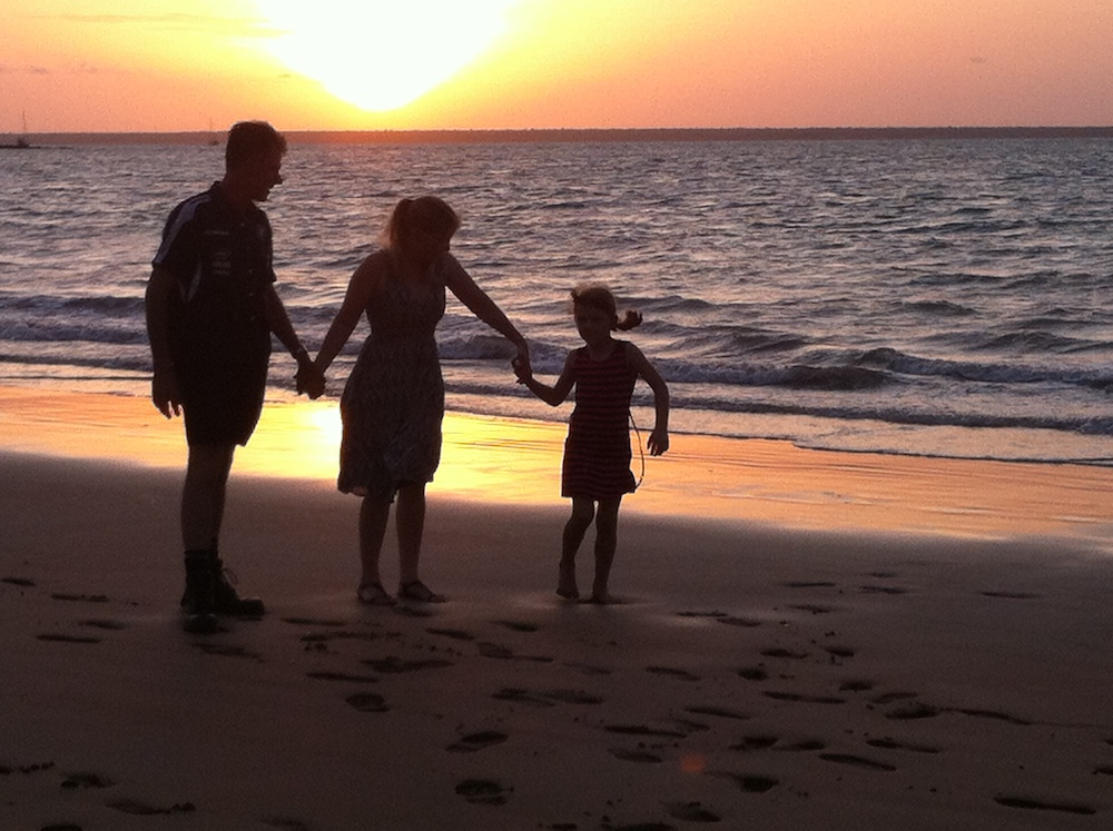 Family walking along the beach at sunset