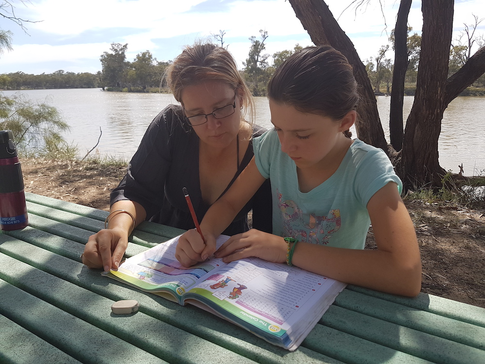 Woman and child doing schoolwork beside the Murray River, VIC Australia
