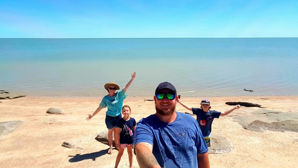 Family posing in front of large body of water in Australia