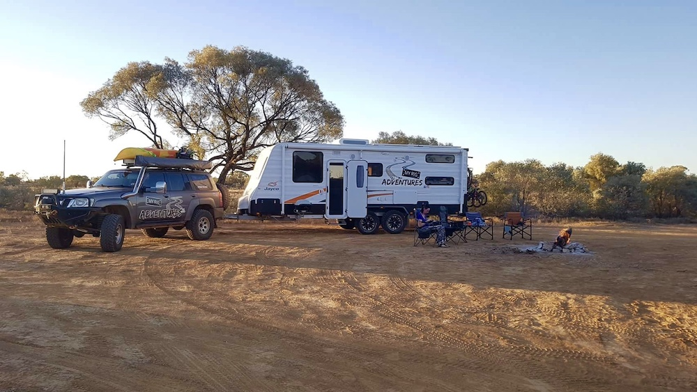 Car and caravan set up for camping in dusty outback Australia