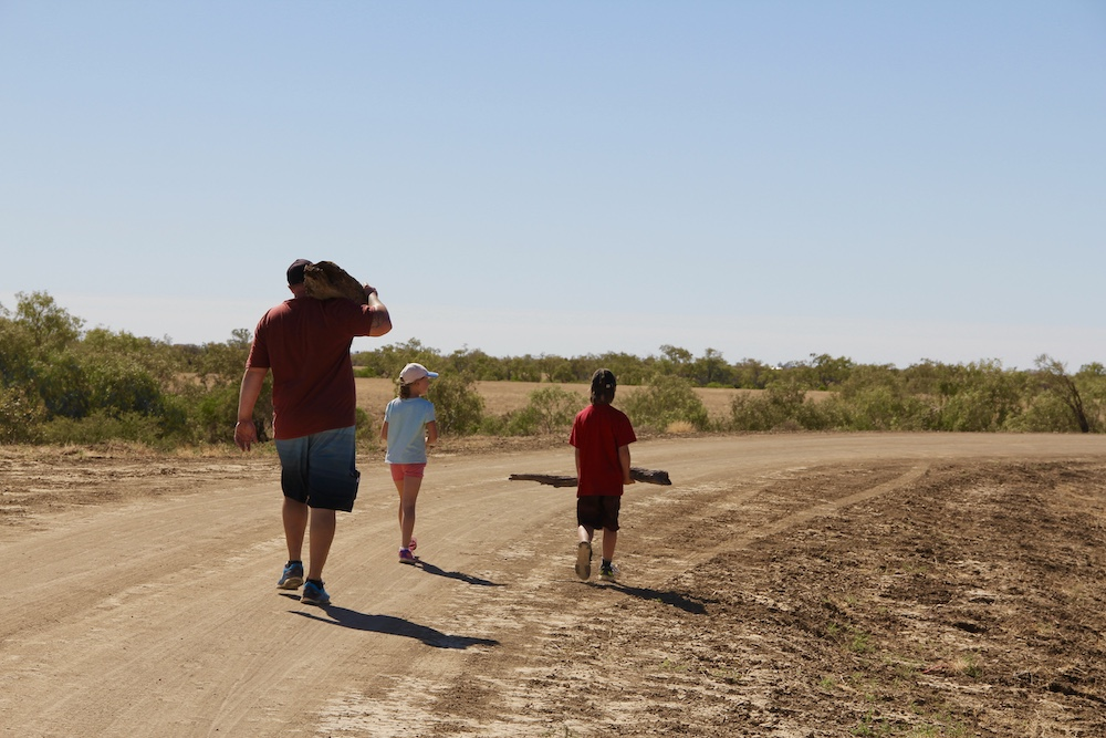 Man and two children walking down a dusty outback Australian road.