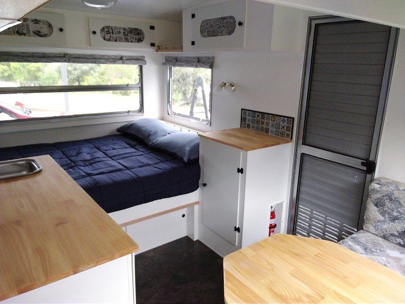 Interior of vintage caravan renovation showing door, storage cabinet and double bed.