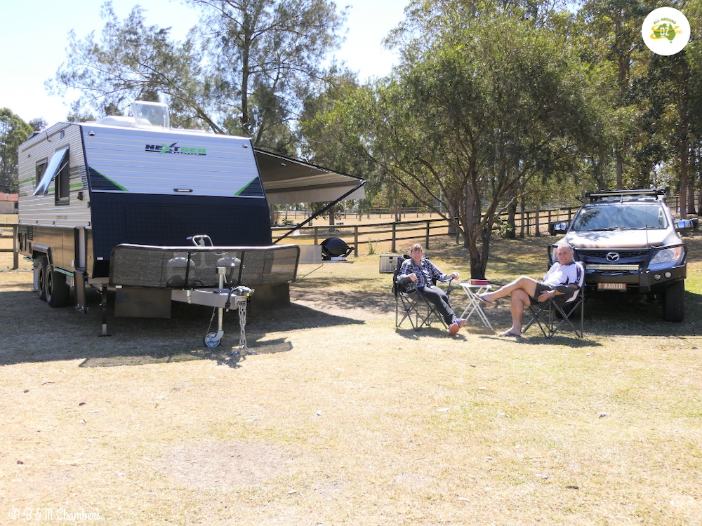 Couple sitting on camp chairs outside their caravan.