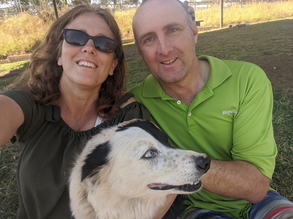 Couple pose for a photo with their Border Collie