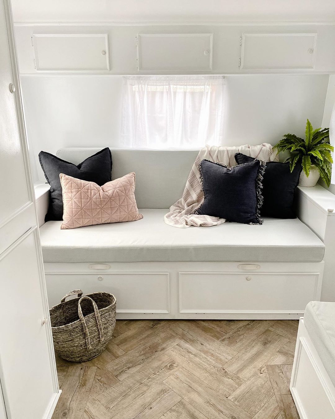 White sitting area with pink and navy blue cushions, in a renovated vintage caravan
