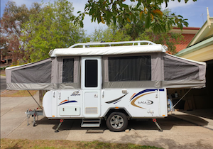 Pop up trailer extended up, ready for camping.