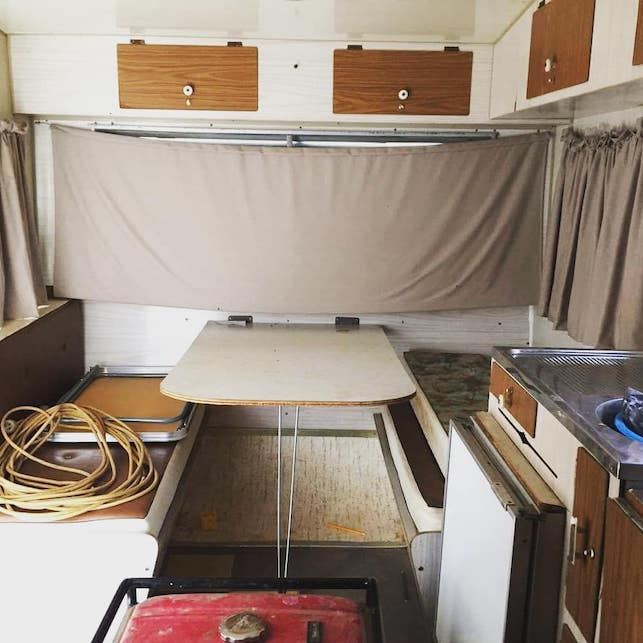 Dinette area inside a vintage caravan that is untidy and worn