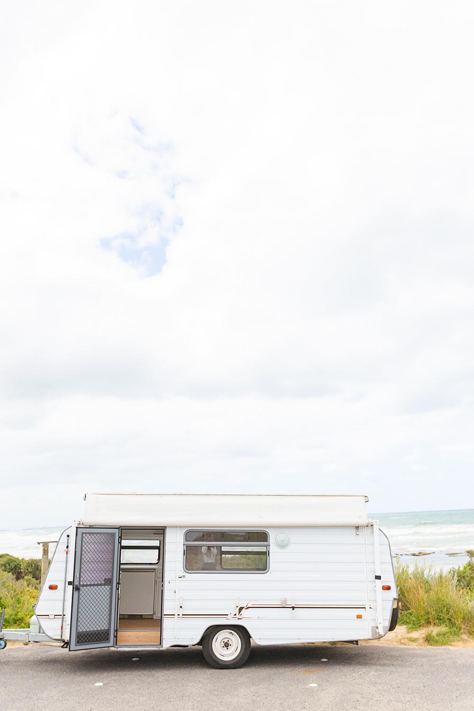 Vintage pop top caravan parked at a beach location