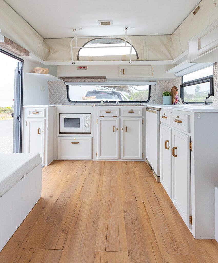 White kitchen cabinets inside a renovated vintage pop-top caravan