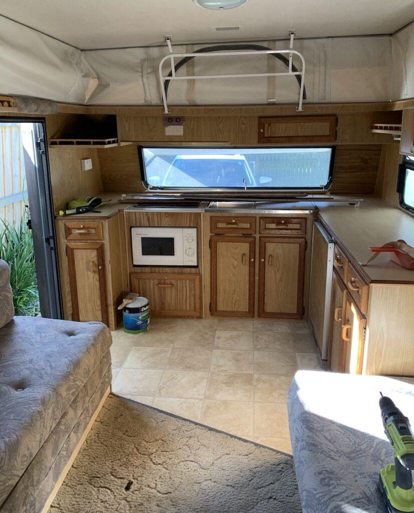 Brown kitchen cabinets inside a vintage pop-top caravan