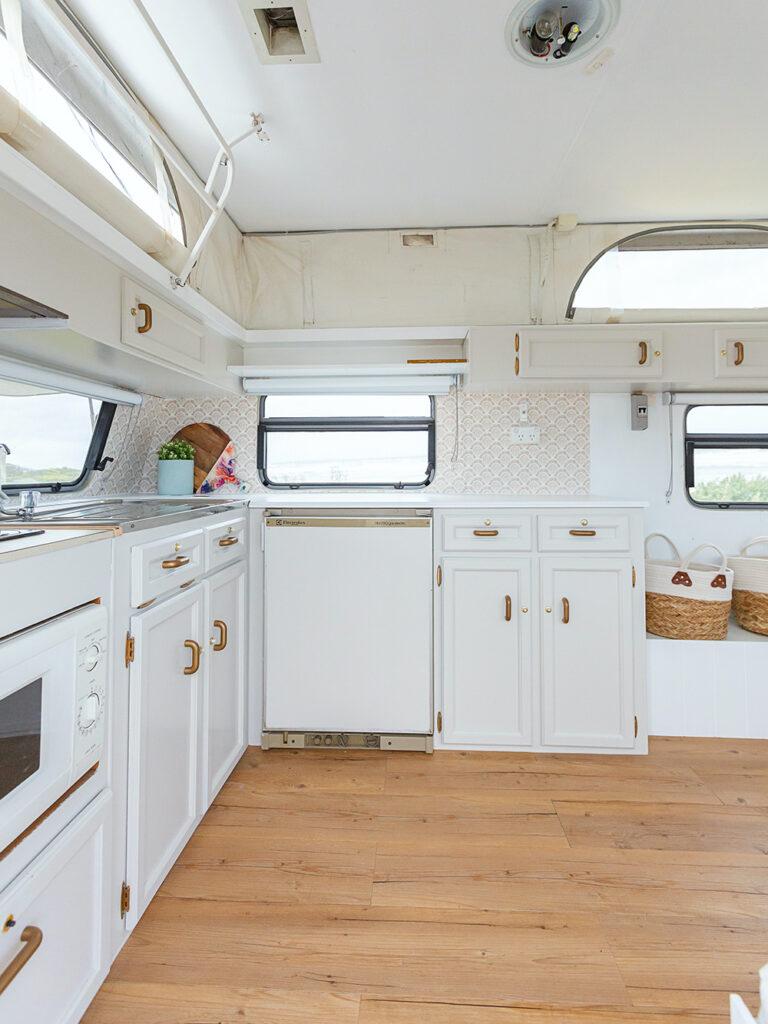 White kitchen cabinets inside a renovated vintage caravan