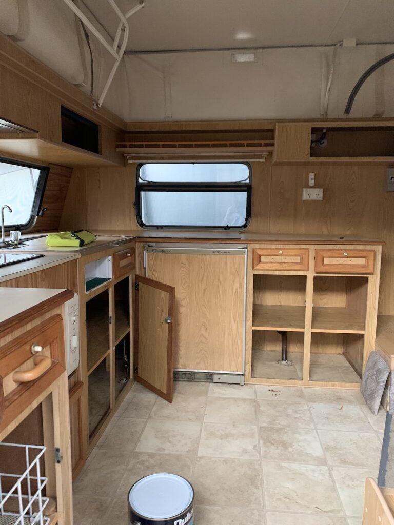 Brown kitchen cabinets inside a vintage caravan