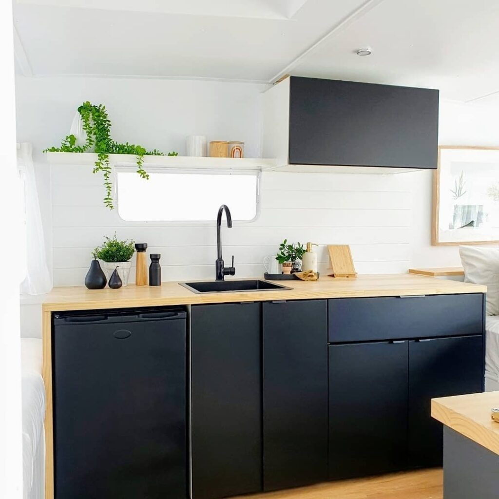Dark blue cabinets and wooden countertop in a renovated caravan.