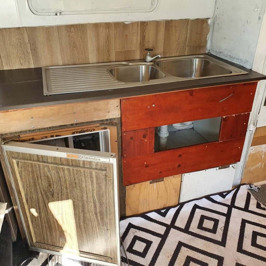 Old and damaged kitchen cabinets in a vintage Viscount caravan before being renovated.