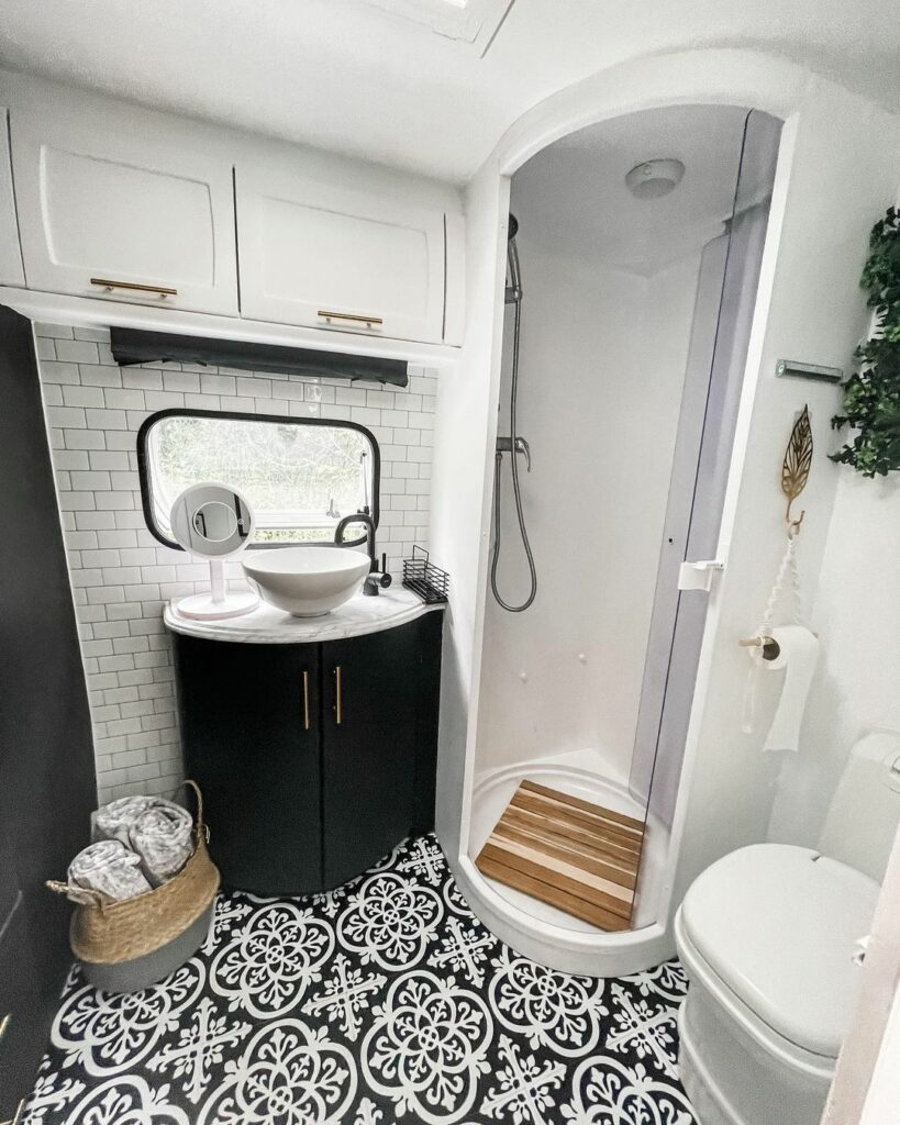 Caravan bathroom after renovation with black cabinets, white walls and shower and black and white floor tiles.