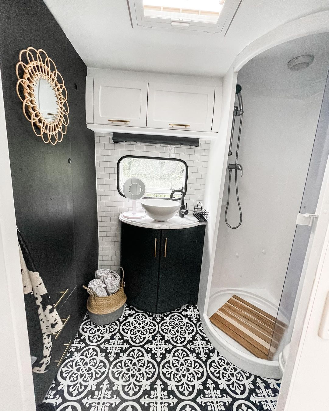 Caravan bathroom with black accent wall and black and white floor tiles.