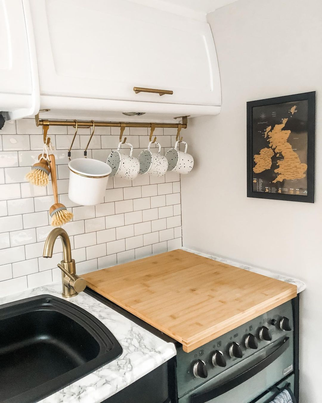 Caravan kitchen with a butchers block cover on the stove top.