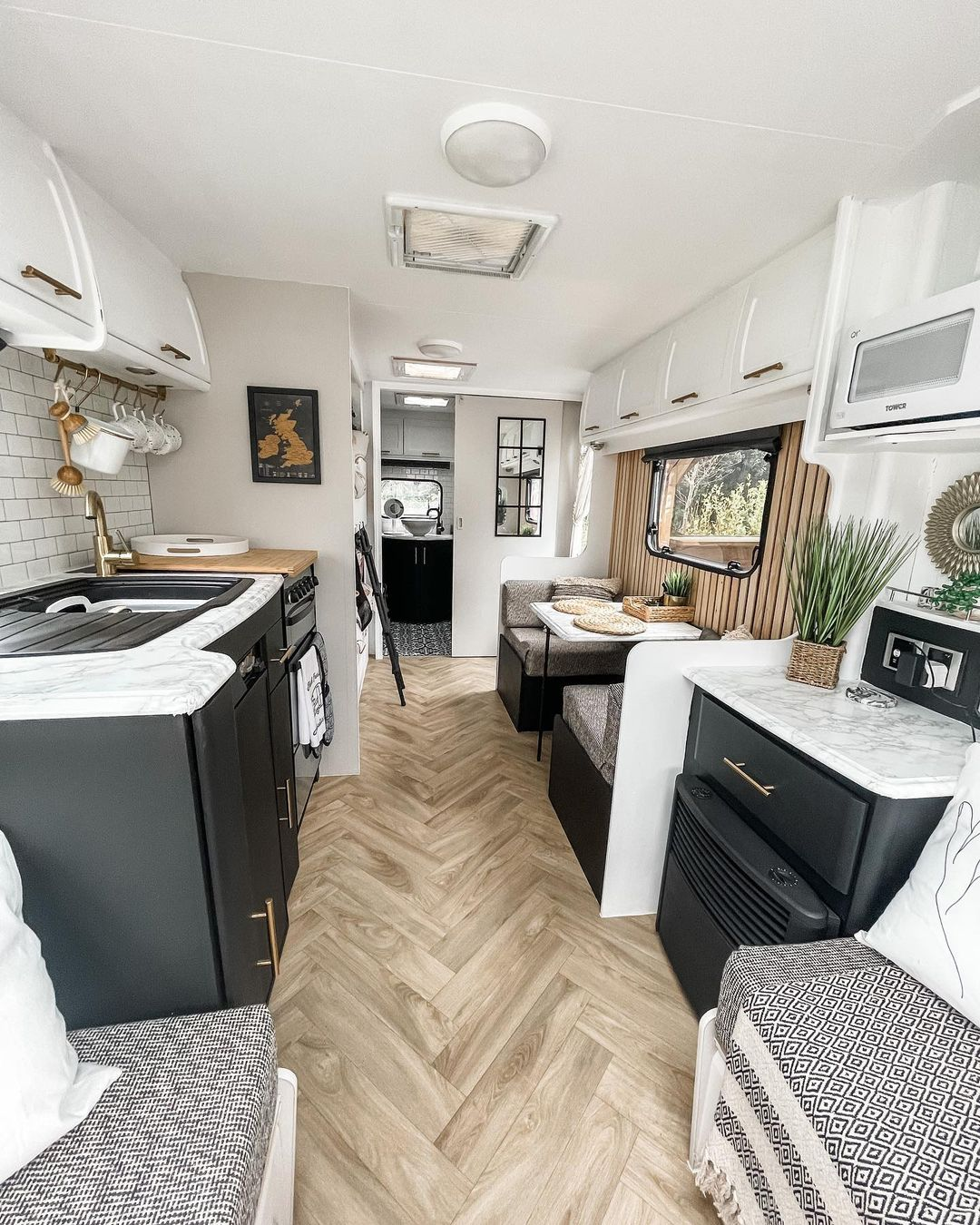 Interior of a renovated caravan with black cabinets and neutral decor.