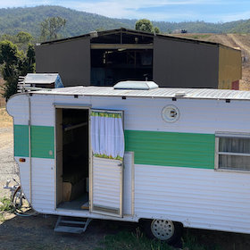 Exterior of vintage caravan with green and white paint work.