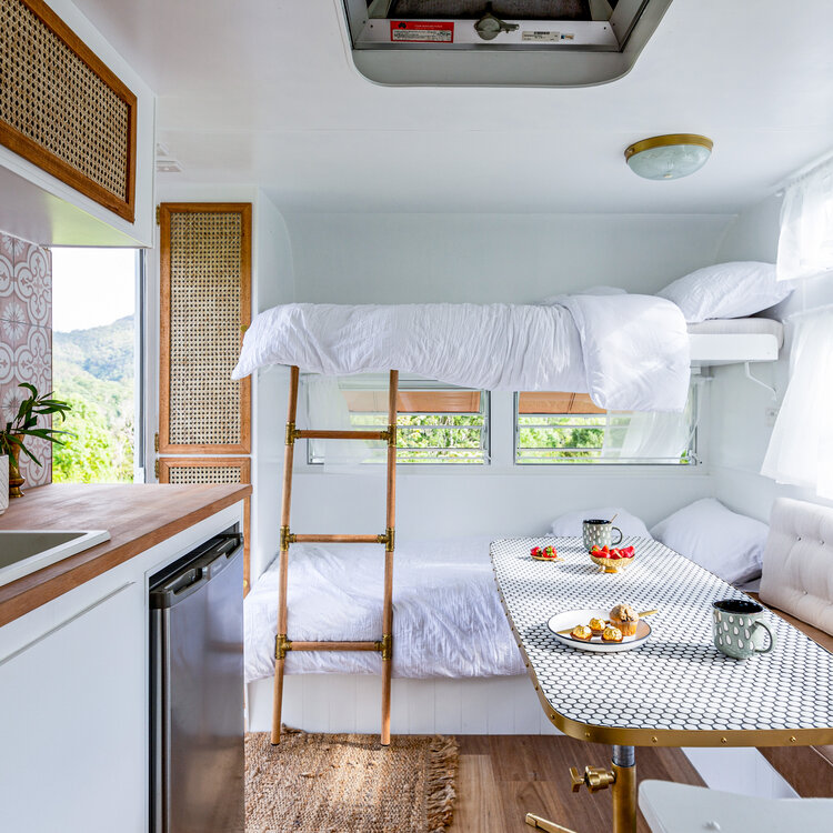 Bunks inside a renovated vintage caravan, with natural and white decor.